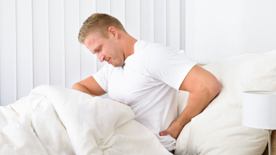 Mann_Rückenschmerzen_Bett - Halten Sie wenn nötig nur kurz Bettruhe. Das Rückenleiden kann dadurch verlängert werden. - © Shutterstock