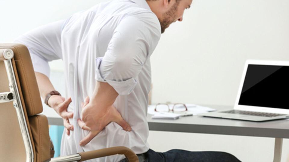 Mann_Rückenschmerzen_Schreibtisch_Laptop - © Shutterstock