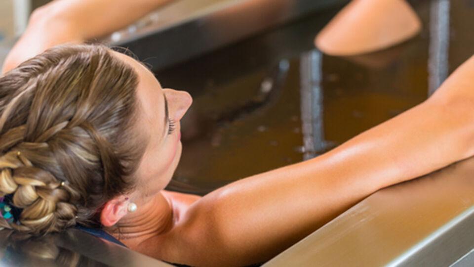 Frau_Schlammbad - Das Resultat von Wärmebehandlungen ist eine bessere Durchblutung, Muskelentspannung und Unterdrückung der Schmerzübertragung. Gut geeignet sind zum Beispiel Schlammbäder. - © Shutterstock