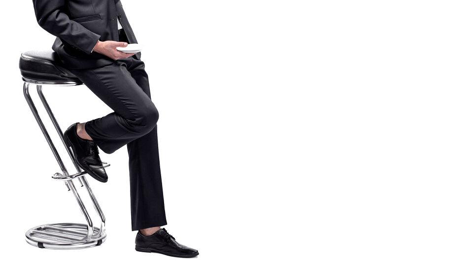 Mann_Stehhocker - Mit einem Stehhocker kann die Haltung immer wieder verändert und so der Rücken entlastet werden. - © Shutterstock