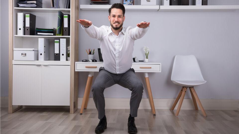 Home office Mann macht Kniebeugen - Ständiges Sitzen ist ungesund. Stehen Sie deshalb öfter mal auf. - © Shutterstock