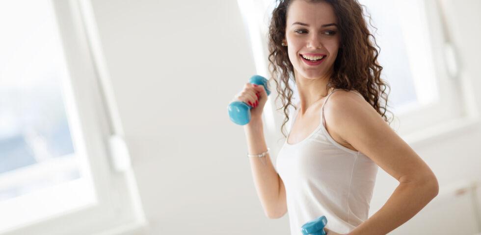 Sport zu hause Frau mit Hanteln - Spaß an Bewegung kann man auch drinnen haben. - © Shutterstock