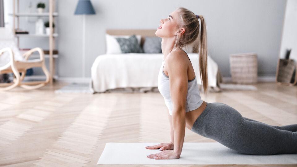 Sport Frau macht Yoga im Wohnzimmer - Yoga wirkt zum Beispiel nicht nur kräftigend, sondern auch entspannend. - © Shutterstock