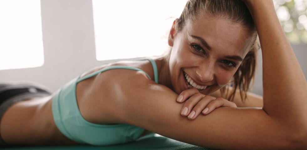 Sport Frau liegt auf Yogamatte und lächelt - Nach dem Sport braucht der Körper Zeit, um sich zu regenerieren. - © Shutterstock
