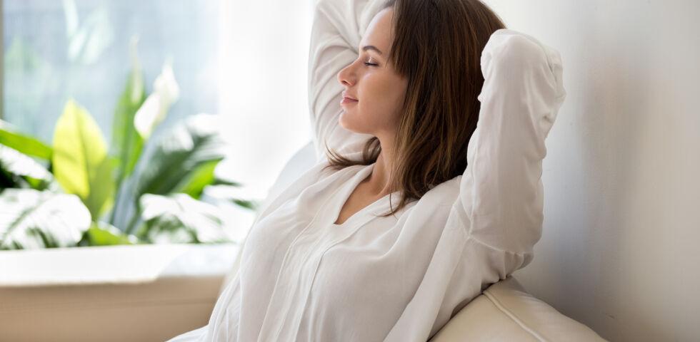 Entspannte Frau sitzt auf Sofa - Es gibt eine ganze Reihe verschiedener Entspannungstechniken. - © Shutterstock