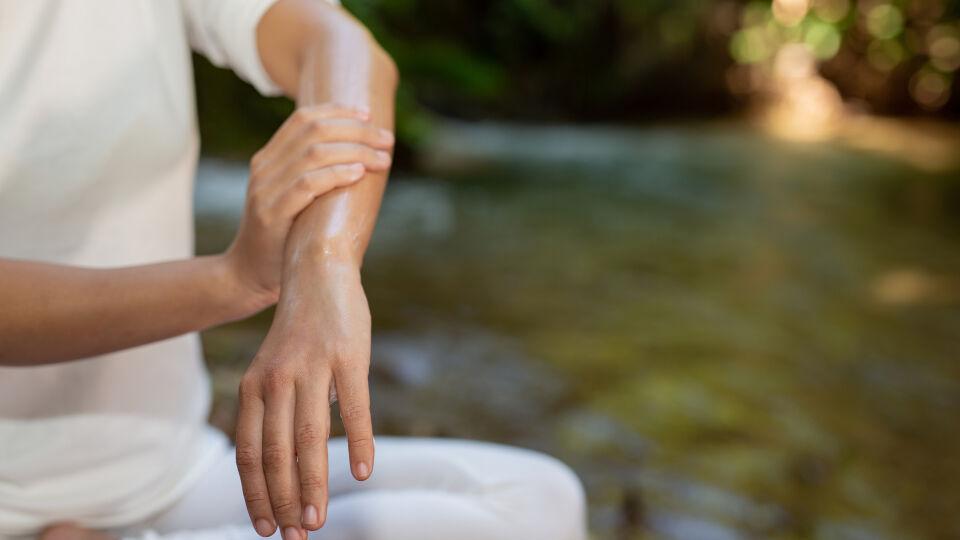 Frau reibt Arm ein_Öl_Mückenschutz_Kosmetik - © Shutterstock