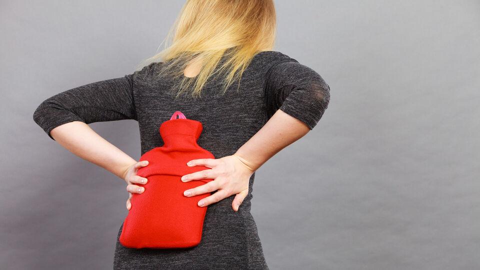 Frau Wärmflasche Rücken - Wärme entspannt die Muskeln und blockiert den Schmerz. - © Shutterstock