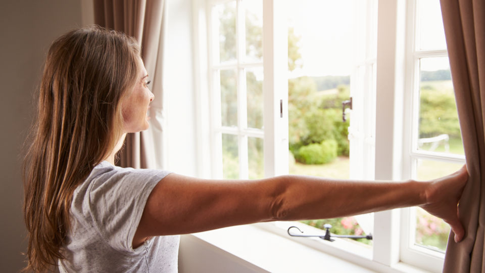 Frau öffnet Fenster zum Lüften - © Shutterstock
