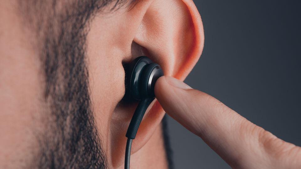 Ohr Kopfhörer - Sehr lautes Musikhören kann dem Gehör schaden und zu einem Tinnitus führen. Bei vielen Kopfhörern kann man in den Einstellungen die Maximal-Lautstärke einstellen – so kann ein versehentliches Erhöhen auf eine gesundheitsgefährdende Lautstärke vermieden werden.