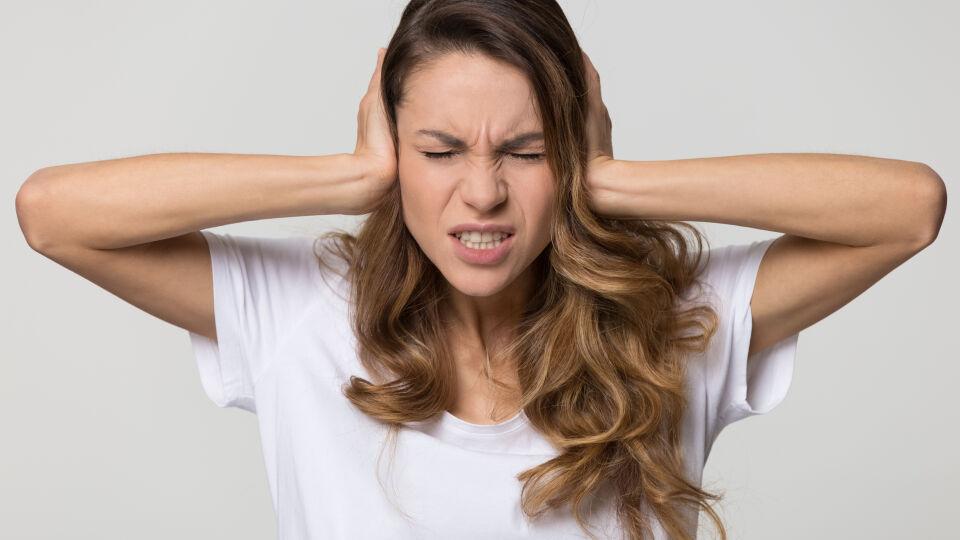 Frau hält sich Ohren zu - Stress und Lärm können einen Tinnitus verschlimmern.