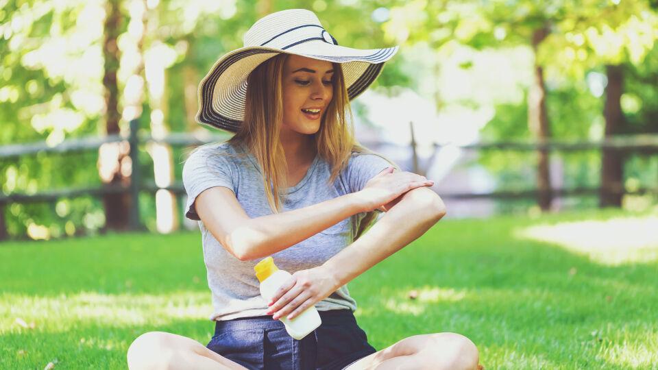 Sonnenschutz Frau sitzt in der Wiese und trägt Sonnencreme auf