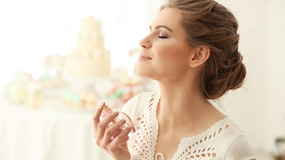 Kosmetik Frau sprüht sich mit Parfum ein - Parfüm trägt man besser erst nach dem Sonnenbad auf.