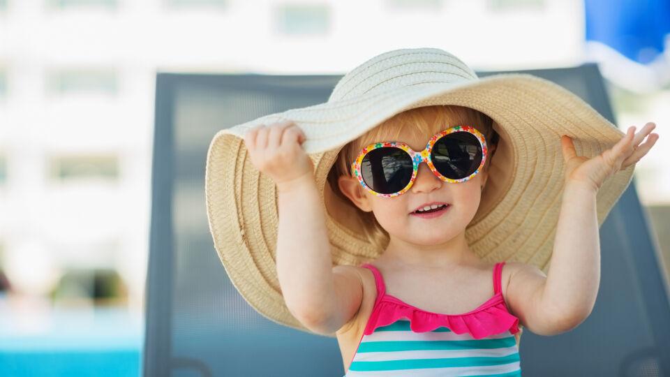 Sonnenschutz Kind sitzt mit Sonnenhut und Sonnenbrille im Schatten - Säuglinge und Kleinkinder sind besser im Schatten aufgehoben.
