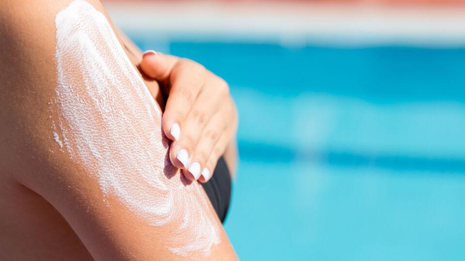 """Sonnenschutz Frau trägt Sonnencreme auf Arm auf - Auch """"wasserfester"""" Sonnenschutz muss erneuert werden."""