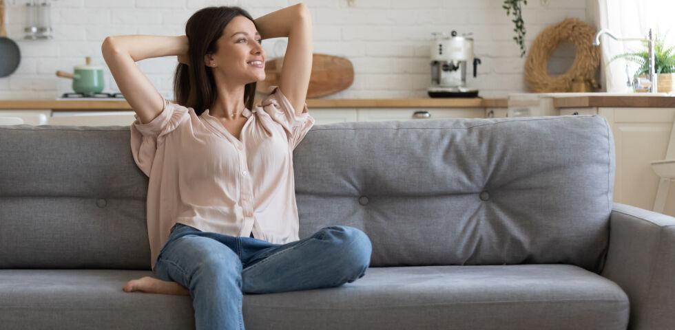 Entspannung_Frau sitzt entspannt auf Sofa - Ständiger Stress schadet unserer Gesundheit.