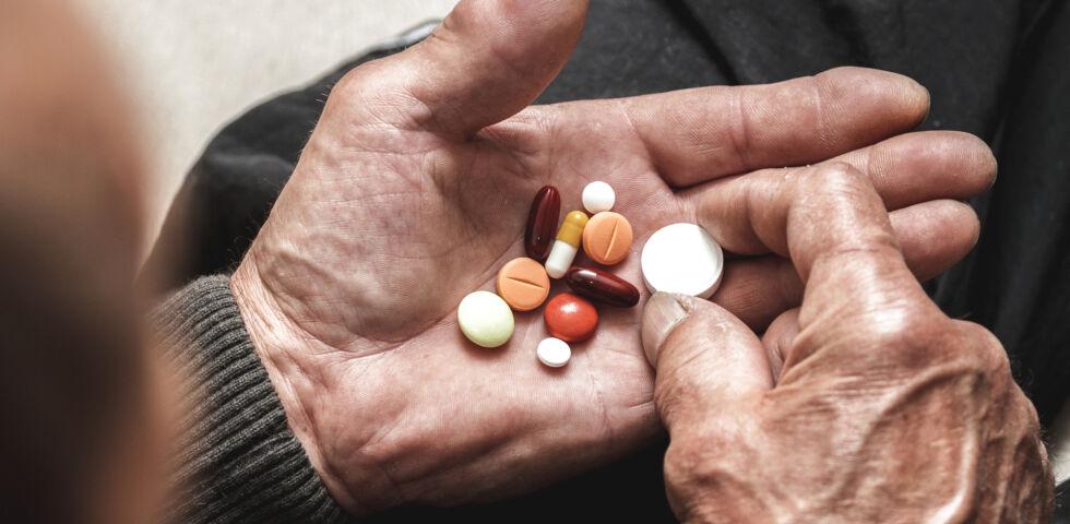 Verschiedene Medikamente in der Hand - Häufig sind es ältere Menschen, die täglich mehrere Medikamente einnehmen müssen.