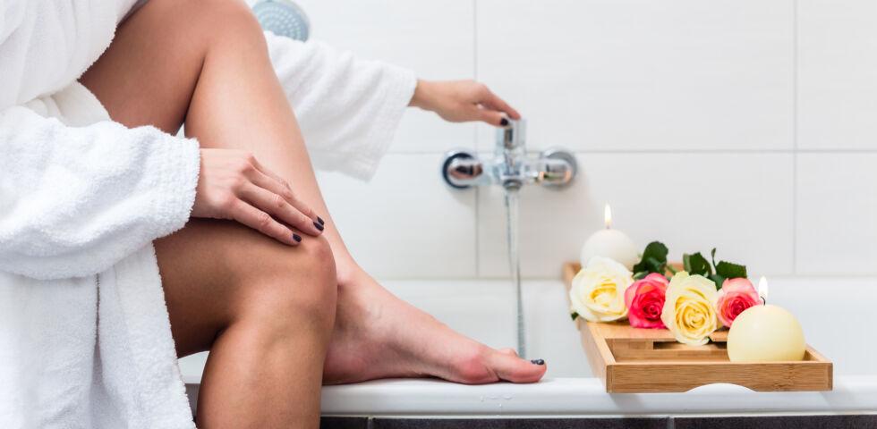 Badewanne_Frau lässt Wasser in die Badewanne ein - Badezusätze können bei Hautproblemen helfen.
