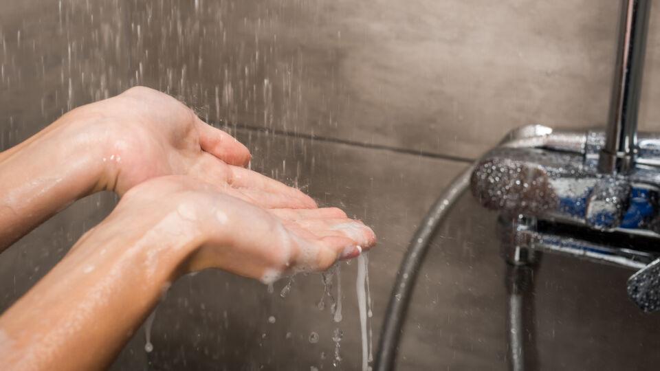 Dusche_Eine Frau hält ihre Hände unter das Duschwasser, um die Temperatur festzustellen - Eine Wechseldusche belebt den Kreislauf.