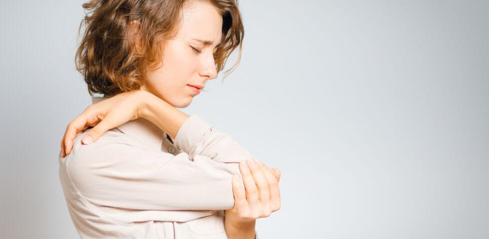 Ellbogen_Eine Frau greift sich auf den schmerzenden Ellbogen - Schmerzhaft: Ein Tennisarm.