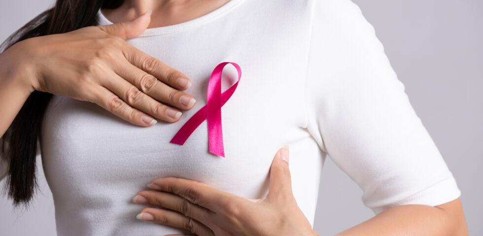 Brustkrebs_Frau trägt Pink Ribbon Band auf dem Tshirt - Mit der rosa Schleife (engl. pink ribbon) zeigt man sich mit allen solidarisch, die an Brustkrebs erkrankt sind.