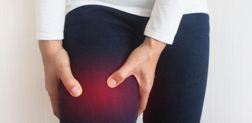 Lipödem_Eine Frau greift sich auf den schmerzenden Oberschenkel - Lipödeme treten häufig im Oberschenkel- und Beinbereich auf.