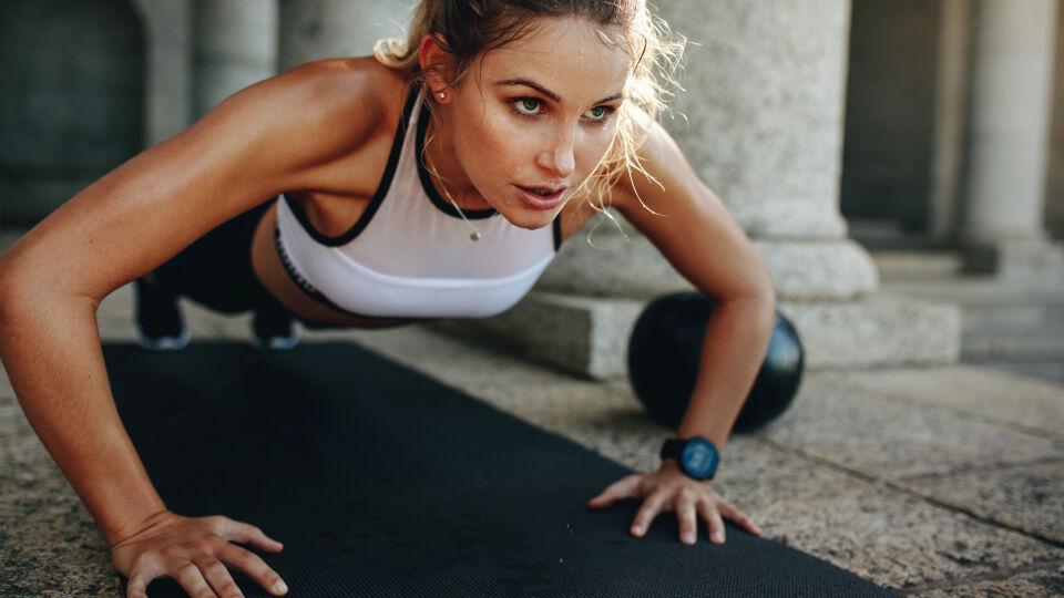Sport_Frau macht Übungen auf Sportmatte - Die intensiven Übungen lassen sich so gut wie auf jede Sportart übertragen.