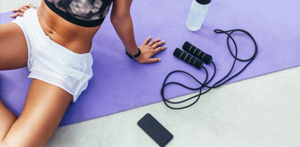 Sport Frau sitzt auf Sportmatte - HIIT bringt Sie garantiert zum Schwitzen.