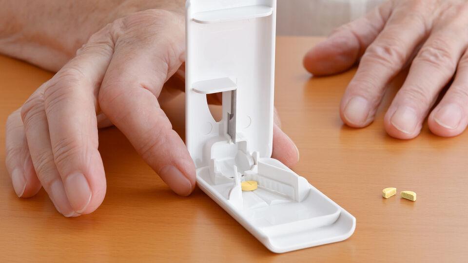 Tablettenteiler - Tabletten dürfen nur dann geteilt werden, wenn Sie eine Kerbe oder ein Kreuz haben. Wenn man sie mit den Händen auseinanderbricht, entstehen oft zwei ungleiche Teile. Mit einem sogenannten Tablettenteiler erhalten Sie hingegen zwei gleich große Teile. - © Shutterstock
