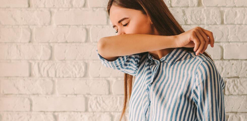 Eine Frau hustet oder niest in den Ellbogen - Man sollte nicht in die Hand, sondern in die Armbeuge husten.
