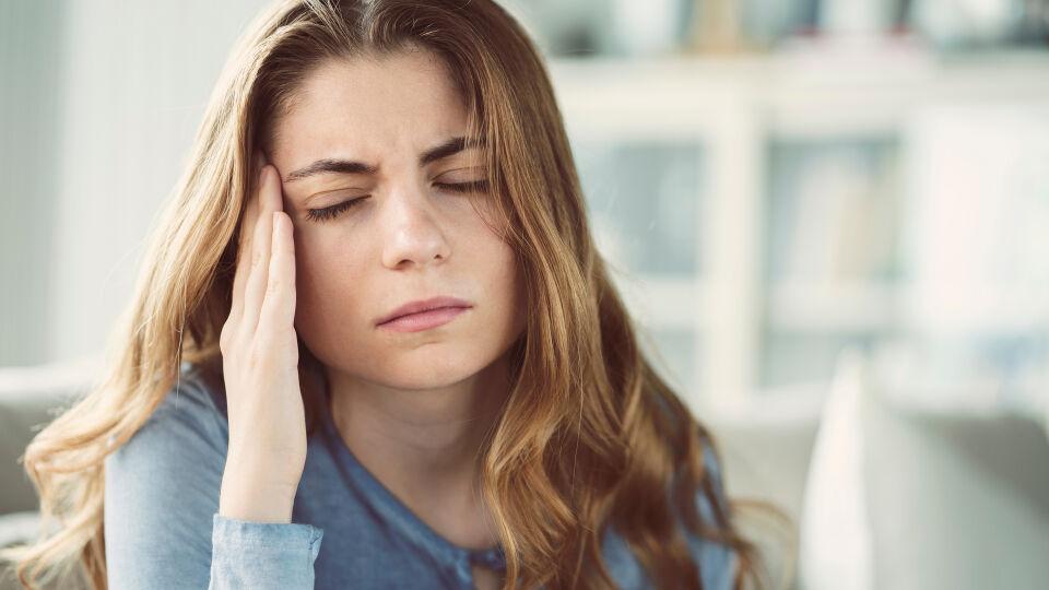 Eine Frau mit Kopfschmerzen - Ein Nährstoffmangel kann zum Beispiel zu Kopfschmerzen oder Konzentrationsproblemen führen.