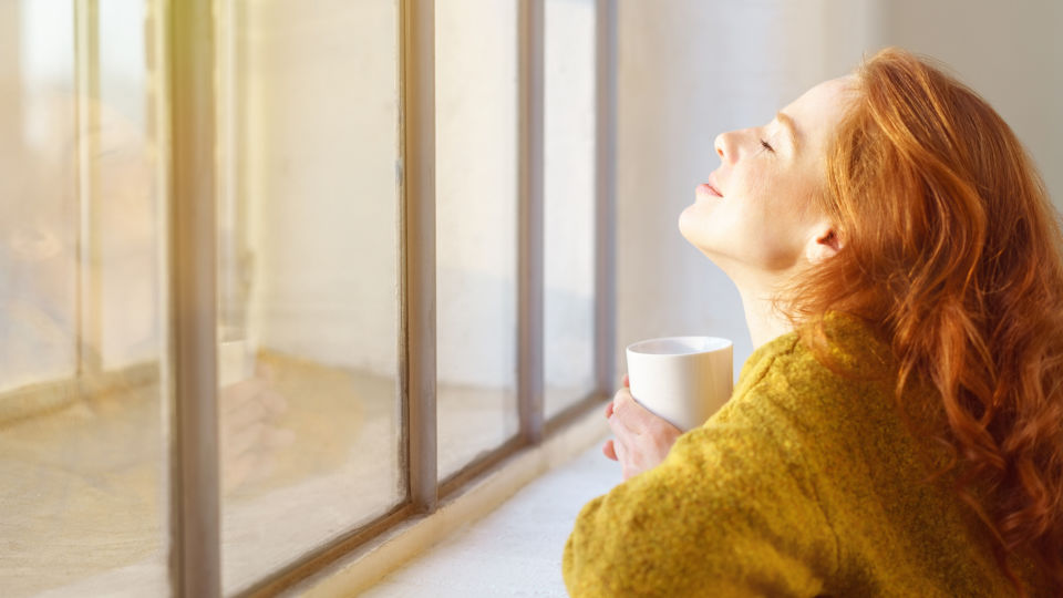 Frau genießt den Sonnenschein - Unser Körper bildet Vitamin D in erster Linie mithilfe von Sonnenlicht.