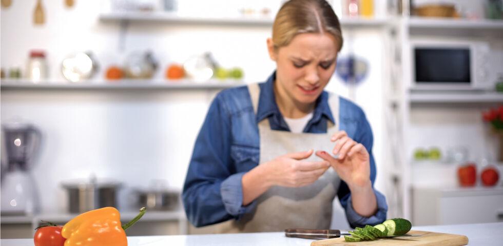 Frau verletzt sich beim Gemüse schneiden_Erste Hilfe - Die meisten Unfälle geschehen im Haushalt.