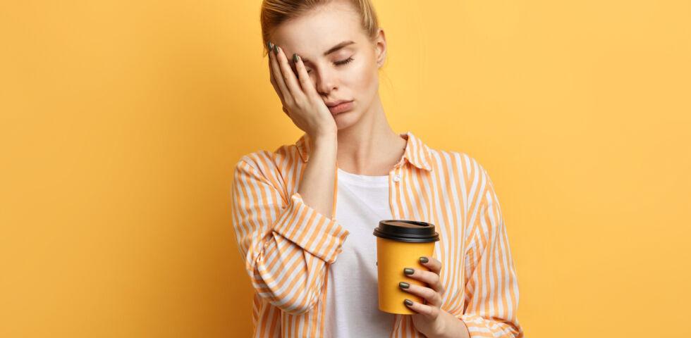 Müde Frau hält einen Kaffee in der Hand - Narkolepsie ist eine neurologische, also vom Gehirn ausgehende, Funktionsstörung.
