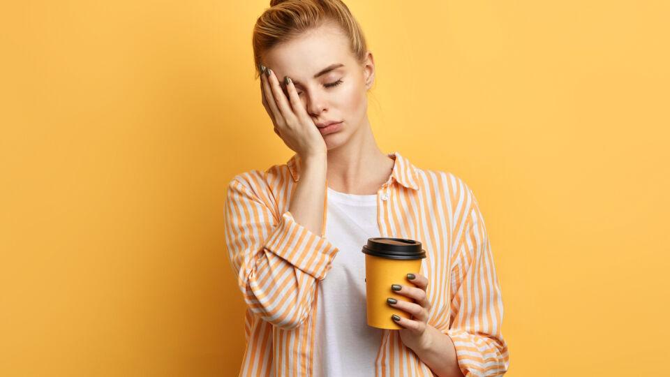 Müde Frau hält einen Kaffee in der Hand