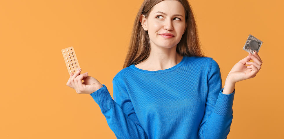 Verhütungsmittel_Frau hält Pille und Kondom hoch - Die Auswahl der Verhütungsmittel ist groß.