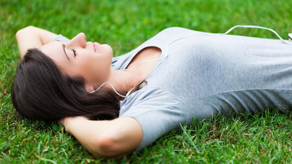 Frau entspannt wiese natur - Planen Sie aktiv Entspannungspausen in Ihren Alltag ein. - © Shutterstock