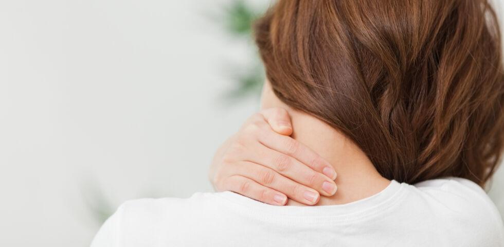 Frau mit Nackenschmerzen - Verspannungen im Nackenbereich können sehr belastend sein.