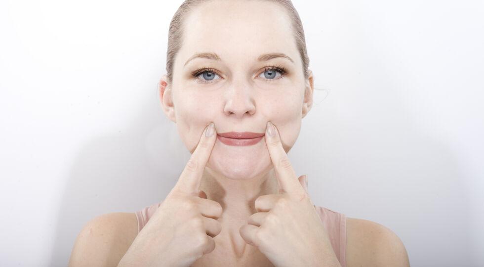 Gesichtsgymnastik 2 - Nasolabialfalten und Lippenfältchen glätten: Pressen Sie die Lippen so fest wie möglich zusammen. Sie können dabei die Mittel- oder Zeigefinger an die Mundwinkel legen, da, wo die Falten entstehen. Spüren Sie, wie der Mundschließmuskel sich anspannt. Lockerlassen und der Entspannung nachfühlen.