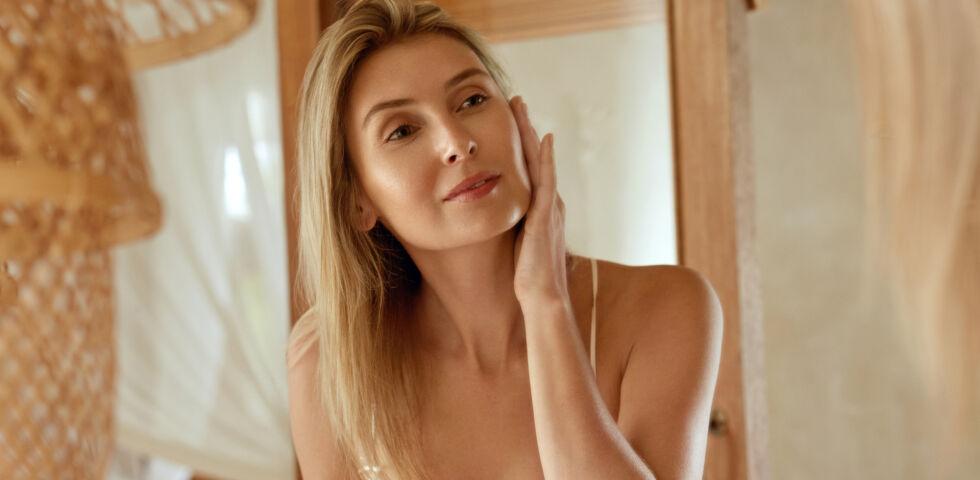Frau sieht in den Spiegel Kosmetik Gesichtspflege