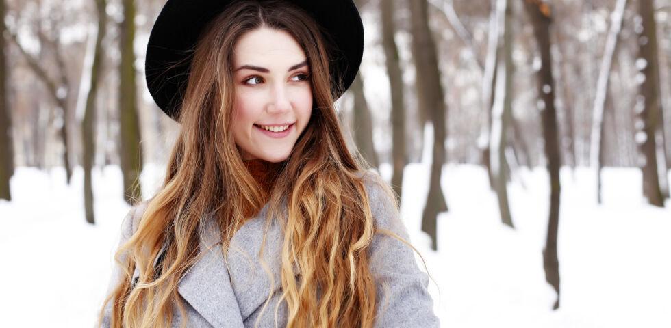 Eine Frau steht lächelnd im Schnee_Winter_shutterstock_373066693 - Kalte Temperaturen und warme Heizungsluft strapazieren unsere Haut.