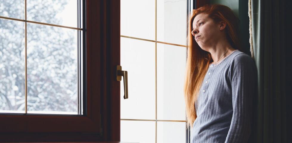 Frau sieht aus dem Fenster_Winter_shutterstock_363383303 - Viele Menschen leiden unter dem Winterblues.