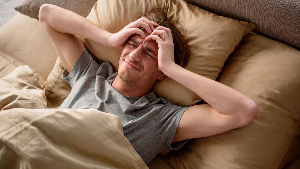 Mann mit Kopfschmerzen_shutterstock_794992039 - Tageslicht wird bei Migräne häufig als unangenehm empfunden. Betroffene fühlen sich in dunklen Räumen wohler.