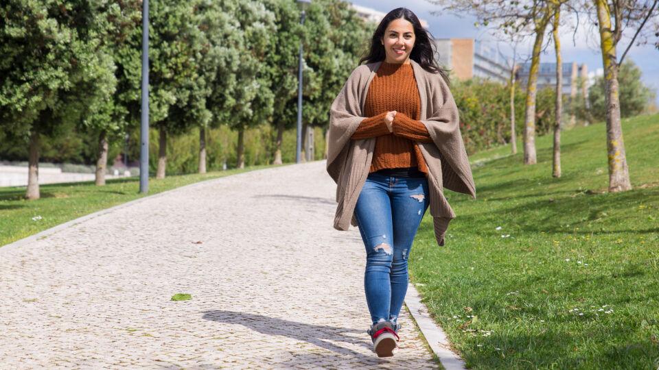 Eine Frau geht fröhlich im Park spazieren_Natur_shutterstock_1385776073 - Schon ein kurzer Spaziergang trägt zu unserem Wohlbefinden bei.