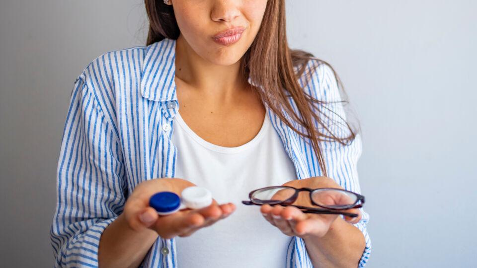 Frau hält Kontaktlinsenbehälter und Brille in der Hand_shutterstock_1799662249 - Kontaktlinsenträger sollten auf die Brille umsteigen, wenn sie Augentropfen oder -salben verwenden.