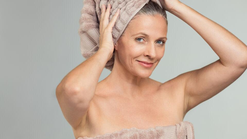 Frau nach dem Haarewaschen mit einem Handtuch auf dem Kopf_shutterstock_1193234599 - Graues Haar hat andere Bedürfnisse.