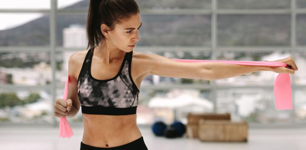 Frau trainiert mit einem Theraband_Sport_shutterstock_1092086012 - Das Theraband ist ein breites Gummiband, das sich für die unterschiedlichsten Fitnessübungen verwenden lässt.