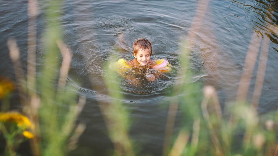 Kind mit Schwimmflügeln im See_Schwimmen_shutterstock_472990165 - Auch im Wasser braucht man Sonnenschutz.