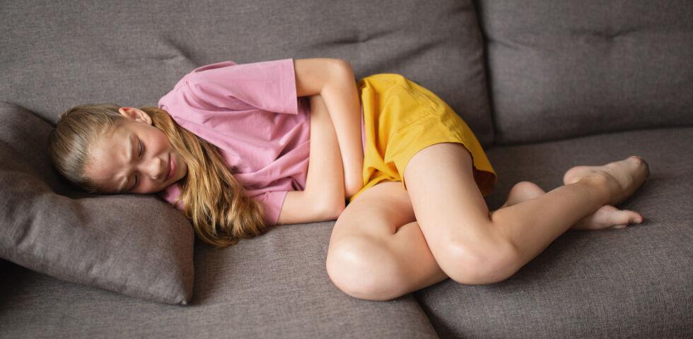 Mädchen liegt mit Bauchschmerzen auf dem Sofa_shutterstock_1995872480 - Magenschmerzen, Völlegefühl und Übelkeit sind typische Symptome einer Gastritis.