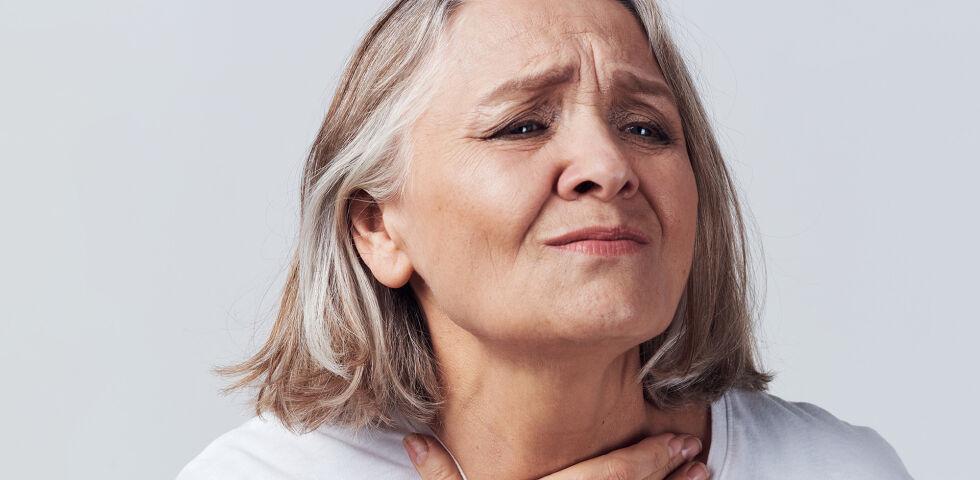 Schluckbeschwerden Seniorin Hals - Schluckstörungen können in jedem Alter auftreten. Wichtig ist hierbei, die Ursache zu finden und rechtzeitig etwas dagegen zu tun. - © Shutterstock