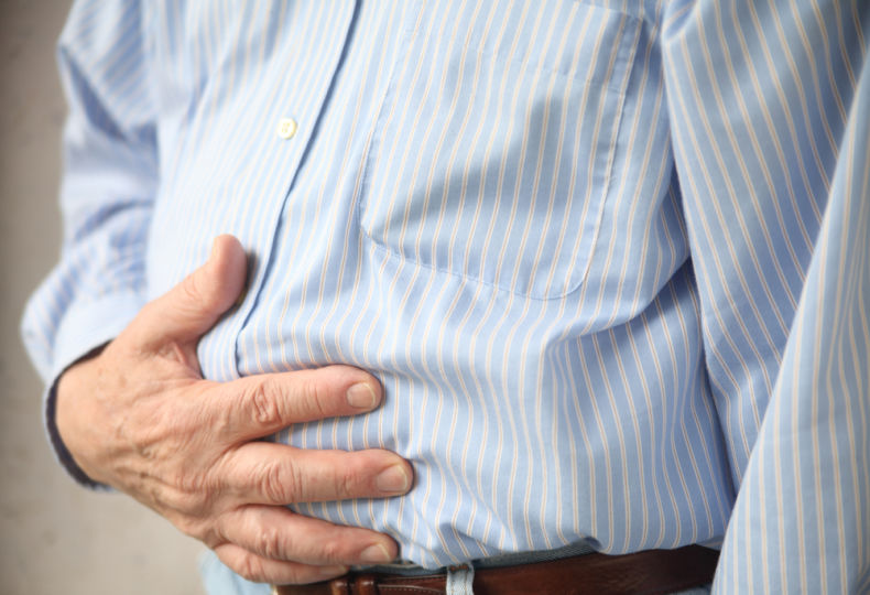 Mann_Bauchschmerzen_Hand auf Bauch - Eine chronische Gastritis kann jahrelang unentdeckt bleiben.